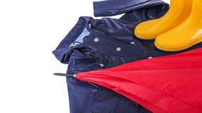 Gummistöveler och regnrock och paraply i regndroppar Royaltyfria Foton