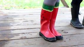 Gummistiefel mit Wassermelonenmuster auf Frauen ` s Beinen stock video
