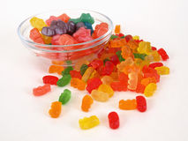 Gummy Bear Treats. Gummy bear shaped candies in and out of a clear glass dish, over a white background Stock Photo