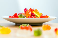 Gummy bears on a white plate and wooden table. Colorful gummy bears Stock Photography
