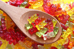 Gummy bears on a wooden spoon. On a gummy bear background. Close-up Stock Image