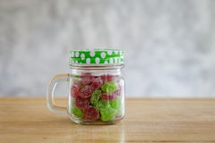 Gummy candies in a glass jar on wooden table. Stock Photos