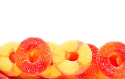 Gummy Candy Background. Isolated gummy orange, yellow, and red candy in bottom of frame with copy space.  Useful for a party, holiday, or festivities background Royalty Free Stock Image