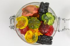 Gummy candy in a jar. Fruity gummy candy of good luck symbols in a glass jar stock photography