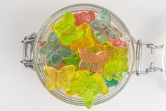 Gummy candy in a jar. Gummy candy butterflies in pink, yellow, green and blue in a glass jar stock photo