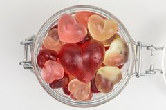 Gummy candy in a jar. Gummy candy of hearts in red, pink and white in a glass jar royalty free stock images