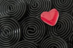 Gummy heart and spirals. Jelly red  heart over liquorice black spirals Royalty Free Stock Photos