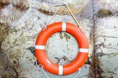 Gumowego pierścionku zrozumienie na Stalowej ścianie Pomarańczowa życia oszczędzania guma Czerwony lifebelt na ścianie blisko oce Zdjęcie Stock