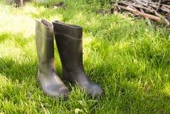 Gumowi buty na zielonej trawie Obrazy Royalty Free