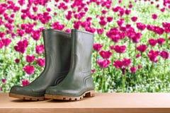 Gumowi buty w kwiatu ogródzie Obrazy Royalty Free