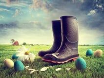 Gumowi buty z Easter jajkami na trawie fotografia stock