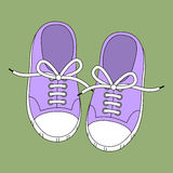 Gumshoes. Purple sneakers on a green background Royalty Free Stock Image