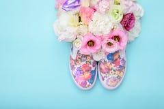 Gumshoes con las flores dentro en fondo brillante Fotografía de archivo