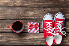 Gumshoes and cup of coffee with gift Stock Photo