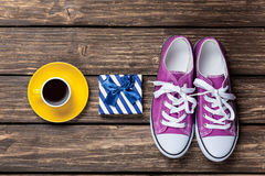 Gumshoes and gift box with coffee cup Stock Image
