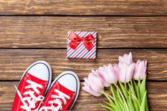 Gumshoes and gift box with tulips Stock Photography
