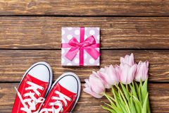 Gumshoes and gift box with tulips Stock Photo