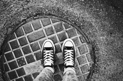 Gumshoes standing an urban manhole cover stock photos