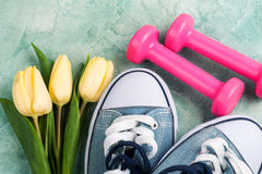Gumshoes, tulips and pink dumbbells Royalty Free Stock Photos