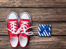 Gumshoes with white shoelaces and gift box Royalty Free Stock Photography
