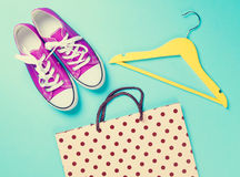 Gumshoes with white shoelaces and hanger with shopping bag Stock Photos