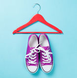 Gumshoes with white shoelaces and red hanger Royalty Free Stock Photos