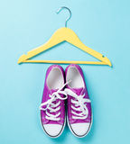 Gumshoes with white shoelaces and yellow hanger Stock Image