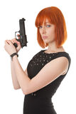 Gun. Beautiful red girl with a gun royalty free stock image