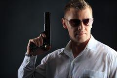 Gun. Portrait of a handsome man holding a gun. Studio shot Royalty Free Stock Image