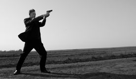 With a gun... A young man standing with a gun in the middle of a field. Low point Stock Photos