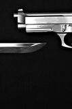 Gun above knife. A black and white image of a sword and pistol pointing at each other on a black cloth Stock Photo