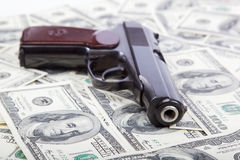 Gun against the dollar bills. Stock Images