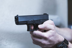 Gun Aimed with Finger on Trigger. Male hands holding a black 9mm pistol with finger on trigger Stock Photography