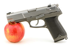 Gun Apple. Pistol and apple studio concept shot for guns and school violence, mild relationship also guns and health royalty free stock image
