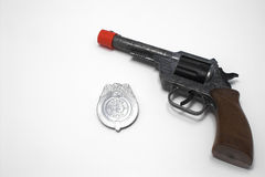 Gun and Badge. A toy police service revolver and badge Royalty Free Stock Photography