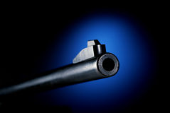 Gun barrel. On black background at angle back lit by blue spot Stock Photography