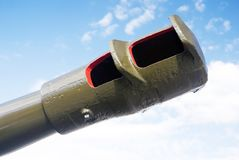 A gun barrel. Blue sky with clouds background. Stock Photo