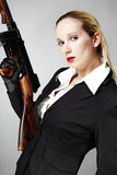Gun and beauty. Mafia style fashion studio portrait - nice young woman posing with Tommy gun for figure and portrait photos in retro criminal style royalty free stock images