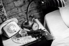 Gun on bedside table. Film Noir Stock Photos