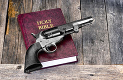 Gun and Bible. Old Western pistol on Holy Bible with room for your type Stock Photo