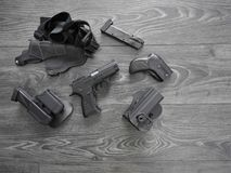 Gun black, spare magazines and leather holster on grey background stock image