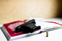 Black gun book and bullet. Detective novel concept. stock image