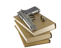 Gun on the book Royalty Free Stock Photos