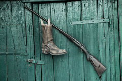 Gun and boots before old wooden background Stock Photo