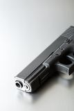 Gun on brushed steel Stock Photography