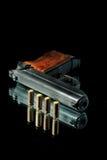 Gun with bullet on a black Stock Photos