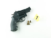 Gun and bullet casing evidence. Aerial view of a revolver with a bullet and a shell casing and a number one evidence marker beside it, against a white background Royalty Free Stock Photos