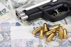 Gun with bullet on czech banknotes Stock Images