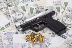 Gun with bullet on czech banknotes Royalty Free Stock Photography