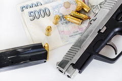 Gun with bullet on czech banknotes Stock Image